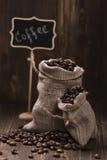 Feijões de café em sacos de serapilheira sobre o fundo de madeira Imagens de Stock