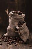 Feijões de café em sacos de serapilheira sobre o fundo de madeira Fotografia de Stock