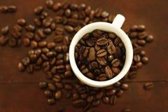 Feijões de café em um copo de café Fotografia de Stock