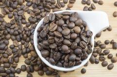 Feijões de café em um copo de café em uma tabela de madeira coberta com o coff Fotos de Stock