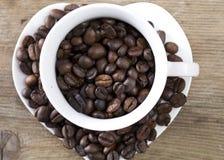 Feijões de café em um copo na tabela de madeira Fotos de Stock Royalty Free