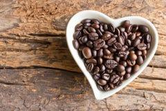 Feijões de café em um coração do copo em de madeira Imagens de Stock