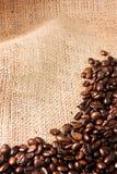 Feijões de café em um fundo da juta foto de stock royalty free