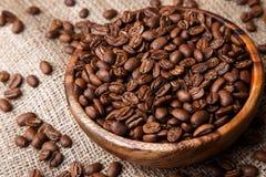 Feijões de café em um prato de madeira Fotos de Stock