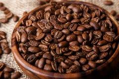 Feijões de café em um prato de madeira Foto de Stock