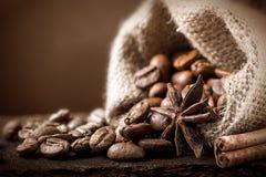 Feijões de café em um saco com canela e badian no fundo marrom Imagem de Stock