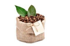 Feijões de café em um saco do pano de saco em um fundo branco com etiqueta vazia imagens de stock