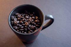 Feijões de café em uma caneca de café Fotografia de Stock