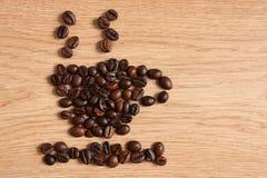 Feijões de café em uma tabela de madeira Imagens de Stock