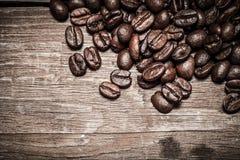 Feijões de café em uma tabela de madeira velha para o fundo Espaço para o tex Foto de Stock