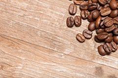 Feijões de café em uma tabela de madeira velha para o fundo Espaço para o tex Fotografia de Stock