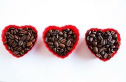 Feijões de café em uns copos do coração Fotos de Stock Royalty Free