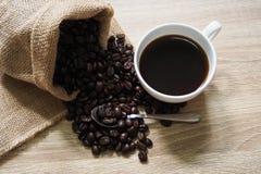 Feijões de café em uns sacos e em um café do americano Imagem de Stock Royalty Free