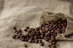 Feijões de café espalhados do bolso de linho Fotografia de Stock