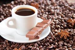 Feijões de café fritados com uma xícara de café e um leite e um anis do café imagem de stock royalty free