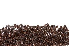Feijões de café isolados no fundo branco com copyspace para o tex Fotografia de Stock Royalty Free