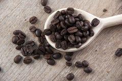 Feijões de café na colher de madeira Fotos de Stock