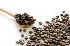 Feijões de café na colher de madeira no fundo branco, café, aroma Fotos de Stock Royalty Free