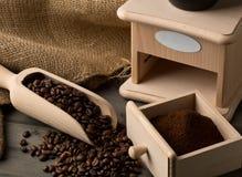 Feijões de café na colher de madeira e no café à terra com feijão de café Fotos de Stock