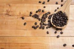 Feijões de café na colher sobre a placa de tabela de madeira Fotografia de Stock