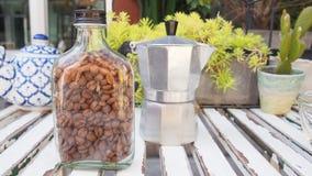Feijões de café na garrafa de vidro com o potenciômetro do chá da chaleira e da cerâmica na tabela de madeira imagens de stock
