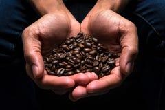 Feijões de café na mão dois Imagens de Stock Royalty Free