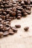 Feijões de café na tabela no fim do pano de saco acima Fotografia de Stock