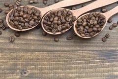 Feijões de café nas colheres na tabela de madeira Fotografia de Stock