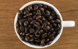 Feijões de café no copo de café no fundo da madeira da tabela Imagens de Stock Royalty Free