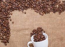 Feijões de café no copo do branco do pano de saco Fotos de Stock Royalty Free