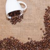 Feijões de café no copo do branco do pano de saco Imagem de Stock