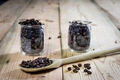 Feijões de café no frasco e na colher de madeira, tabela de madeira Imagens de Stock Royalty Free