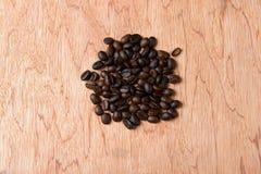 Feijões de café no fundo de madeira imagens de stock