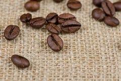Feijões de café no fundo de serapilheira Imagens de Stock Royalty Free