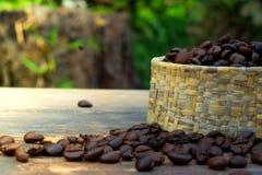 Feijões de café no volume na tabela de madeira e em uma luz suave Fotos de Stock Royalty Free