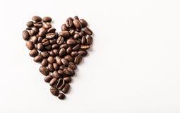 Feijões de café orgânicos roasted de comércio justos dados forma como um coração no whi fotografia de stock royalty free