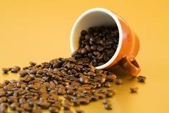 Feijões de café que caem da caneca Fotos de Stock Royalty Free