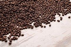 Feijões de café que derramam em uma tabela branca Fotos de Stock Royalty Free