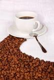 Feijões de café que fazem um trajeto a um copo branco Fotos de Stock