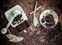 Feijões de café que saem do copo com fundo do moedor fotos de stock royalty free