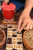Feijões de café recentemente à terra em um filtro do metal e feijões de café com chaleira vermelha Fotos de Stock Royalty Free