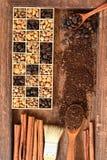 Feijões de café recentemente à terra em um filtro do metal e feijões de café diferentes em uma caixa quadrada Imagem de Stock Royalty Free