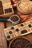 Feijões de café recentemente à terra em um filtro do metal e feijões de café diferentes em uma caixa quadrada Fotografia de Stock