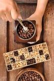 Feijões de café recentemente à terra em um filtro do metal e feijões de café diferentes em uma caixa quadrada Foto de Stock