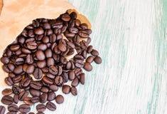 Feijões de café Roasted em uns sacos de papel no fundo de madeira Fotos de Stock Royalty Free