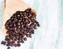 Feijões de café Roasted em uns sacos de papel no fundo de madeira Fotografia de Stock Royalty Free