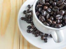 Feijões de café Roasted no copo consideravelmente branco na tabela de madeira Fotos de Stock Royalty Free