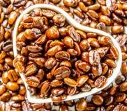 Feijões de café Roasted no copo do branco do coração fotos de stock royalty free