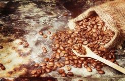 Feijões de café Roasted no saco pequeno na superfície de metal foto de stock