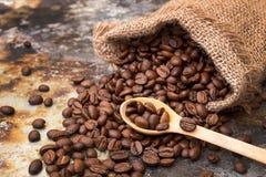 Feijões de café Roasted no saco pequeno na superfície de metal imagem de stock